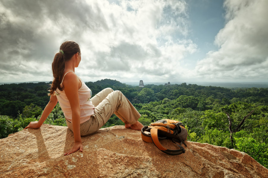 Woman looks at a landscape from atop a rock