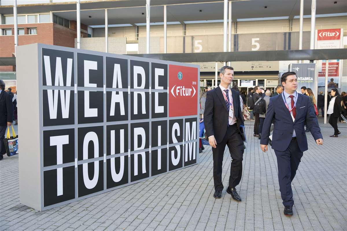 two men walk past We Are Tourism sign at FITUR