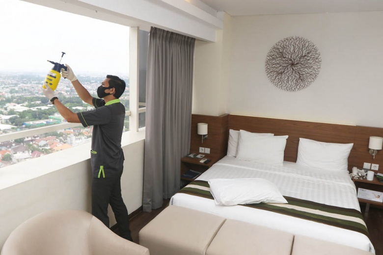 man cleaning hotel room window