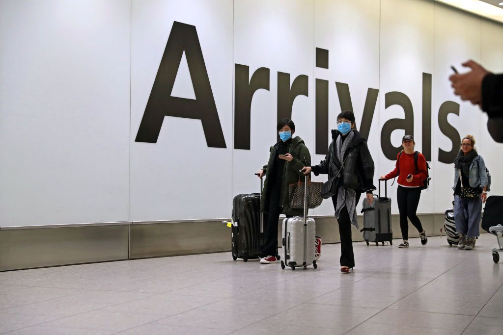 passengers with masks arriving at airport