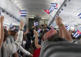 inside a Cuba flight, passengers with Cuban flags