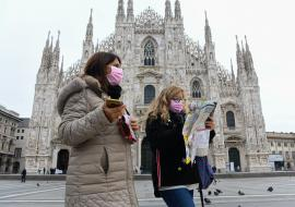 two women wear masks and stand in front of church