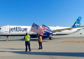 JetBlue plane on tarmac, US and Cuban flags