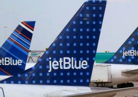 three JetBlue aircraft tails at an airport