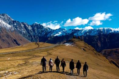 7 people walking in a landscape