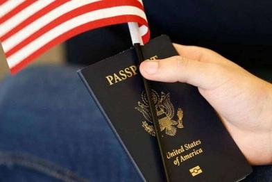 hand holds US passport and flag
